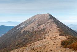 Impressive mountain peak Sokolov kamen (Hawk's rock) on Suva planina (Dry mountain), Serbia, during autumn season and hikers going up the track