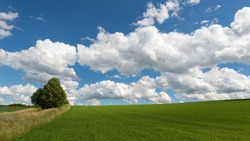Impressive sky with cumulus clouds over a rural landscape. Germany, Hessen near Kirtorf