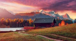 impressive sunset at Alps. Wonderful Picturesque landscape with colorful dramatic sky over the mountain valley with fairy lake and Zugspitze on background. Typical Alpine hut on meadow under sunlit.
