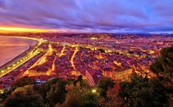 Impressive sunset view of Nice sea waterfront from the castle hill, with tumultuous sky and clouds, and warm light