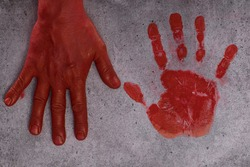 imprint of a bloody palm on cement