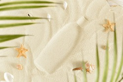 Imprint of a bottle of sunscreen oil on white sand with seashells. Suntan Skin protection on a beach vacation concept. Beach with shells and palm leaves. Use the cream to skincare in the hot sun.