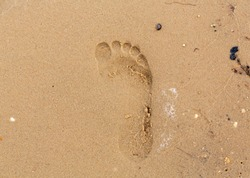 Imprint of the foot of a child in heavy sand in the summertime.