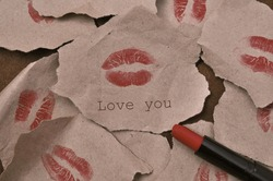 imprint of woman's lips in red lipstick with inscription love you on wrapped paper, many kisses