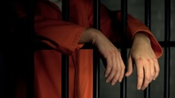 Imprisoned man with wounds on arms standing near bars, incarceration after fight