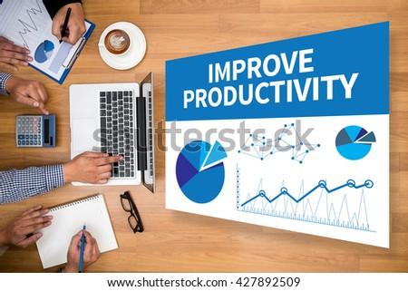 IMPROVE PRODUCTIVITY Business team hands at work with financial reports and a laptop