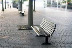 Improvement of public space. Bus station place for waiting. Urban bench or seat. City bench with backrest. Rest and relax. Empty benches in street. Quarantine and pandemic concept. Vandal proof bench.