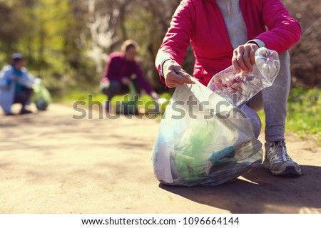 Improving environment. Kind eco-friendly volunteers holding packets and gathering garbage
