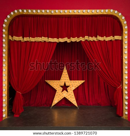 Improvised theatrical stage with a red velvet curtain and a big star with luminous lights. Concert hall. Star performance #1389721070