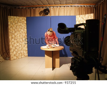 Improvised TV studio with blue background and a TV camera