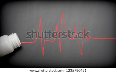 Impulses in red drawn on slate go out of a bottle of pills, conceptual image #1235780431