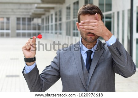 Impulsive businessman playing darts with his eyes closed