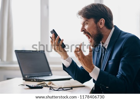 impulsive man yelling into the phone laptop in the background