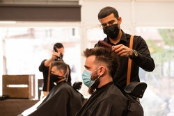 in a barber shop barbers cut the hair of two clients during the pandemic, they wear a coronavirus protective mask. they are caucasian and latin, multiethnic.