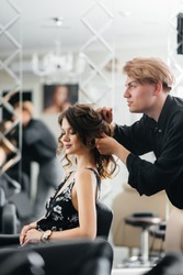 In a beautiful, modern beauty salon, a professional stylist makes a haircut and hairstyle for a young girl. Beauty, and fashion