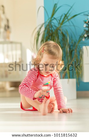 in a beautiful sunny apartment the cute child sits barefoot on the floor and plays #1011815632