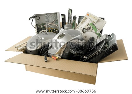In a cardboard industry  box  are old faulty broken audio and video electronics. Devices are prepared for recycling on garbage. Isolated with patch. All logos and trademarks is removed