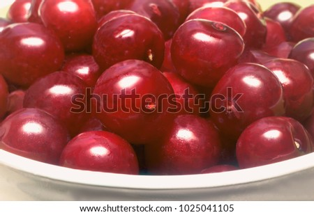In a ceramic vase on the table large ripe cherry dark cherry color and two red cherries with green cuttings. Presents major plan. #1025041105
