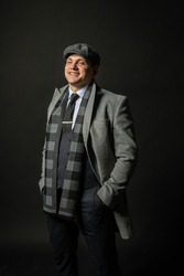in a coat and a cap a scarf Young male three piece suit business man, attractive casual happiness model, successful lonely background black bodybuilder