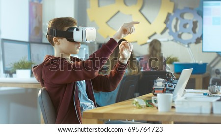 In a Computer Science Class Boy Wearing Virtual Reality Headset Works on a Programing Project.