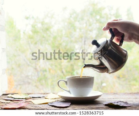 in a female hand, a coffee pot from which coffee is poured into a white cup. Window. Natural light. Concept - morning coffee, coffee time. Foto stock ©