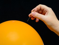In a female hand a sewing needle. The needle is above the surface of an orange balloon. Concept-criticism, debunking of false authorities