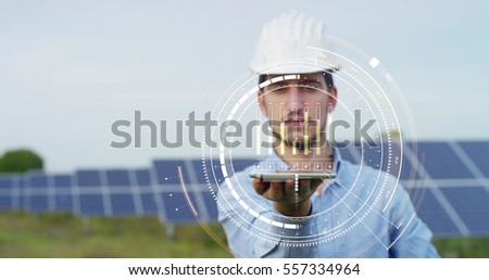 In a field photovoltaic solar panels an engineer, thanks to holography and augmented reality, check their operation with the sun and their productivity. Concept:renewable energy,technology,electricity