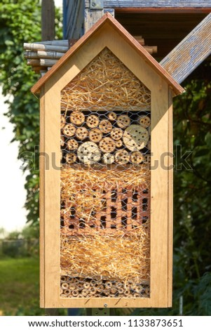 In a garden hangs an insect hotel in the sunlight. #1133873651
