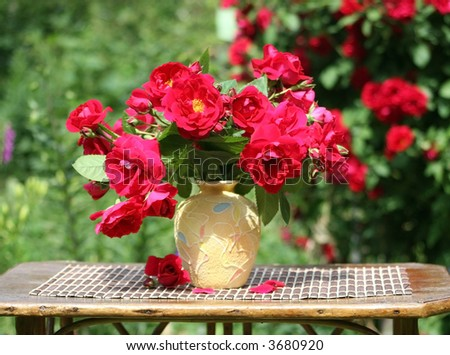 In a garden there is a little table with a bouquet of  red roses. Summer.