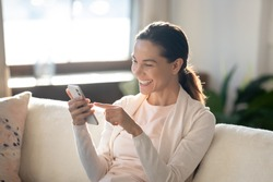 In a good mood. Laughing millennial woman taking cute selfie on couch at home on mobile phone webcam, having funny video conversation by video link, watching joyful photos or clips online using wifi