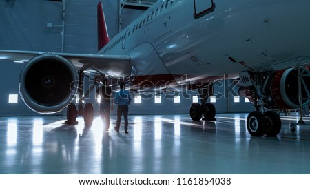 In a Hangar Aircraft Maintenance Engineer Shows  Technical Data on Tablet Computer to Airplane Technician. They Walk Alongside Clean Brand New Plane.