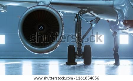 In a Hangar Aircraft Maintenance Engineer/ Technician/ Mechanic Visually Inspects Airplane's Jet Engine.
