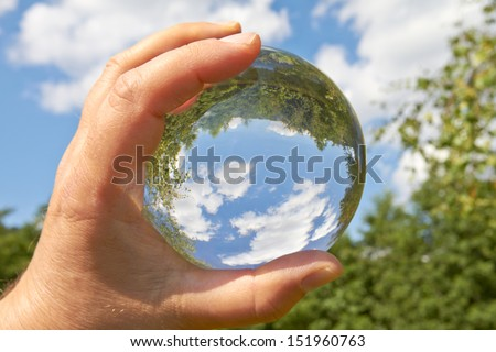 In a held glass ball can you seen the landscape behind her.