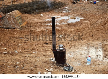 In a muddy site, construction site workers are brewing Turkish Tea on an open air stove in classic style teapot