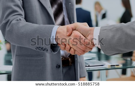 in a sign of cooperation, the partners shake hands after signing