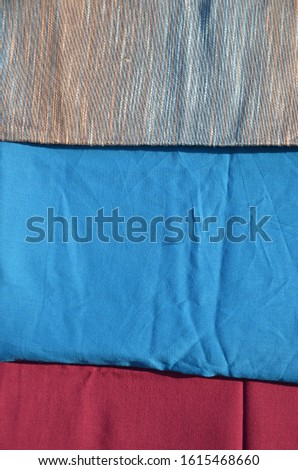 In a textile shop, there are fabrics of various colors and various materials