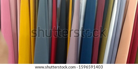 In a textile shop, there are fabrics of various colors and various materials, such as fabric, lace, satin, linen