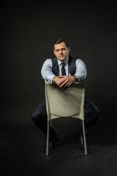in a three-piece suit on a chair Young male three piece suit confident model, portrait happy. Seller lonely background black bodybuilder