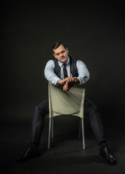 in a three-piece suit on a chair Young male three piece suit male adult handsome, young isolated white. Happiness city, success lonely background black bodybuilder