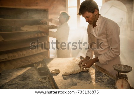 In a traditional bakery, bakers prepare the dough for the bread. The morning sun comes in through the window ストックフォト ©