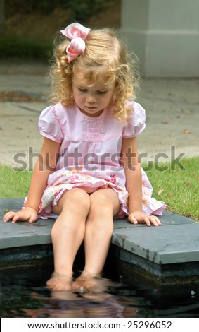 In a world of her own, small blond haired child wet her feet in pool.  Pink dress and hairbow.