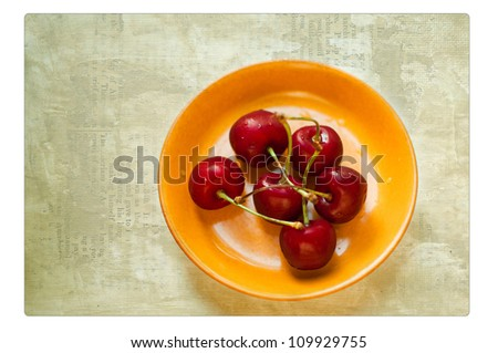 in a yellow plate the ripe red cherry lies