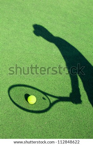 in action on a tennis court (conceptual image with a tennis ball lying on the court and the shadow of the player positioned in a way he seems to be playing it)