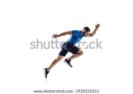In air. Caucasian professional male athlete, runner training isolated on white studio background. Muscular, sportive man. Concept of action, motion, youth, healthy lifestyle. Copyspace for ad.