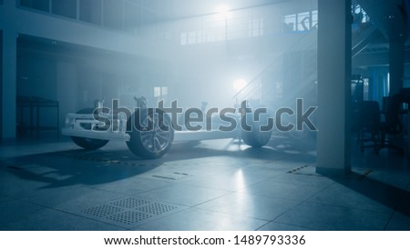 In Automotive Innovation Facility Silhouette of Electric Car Platform Chassis with Backlight. Prototype Includes Wheels, Suspension, Hybrid Engine and Battery