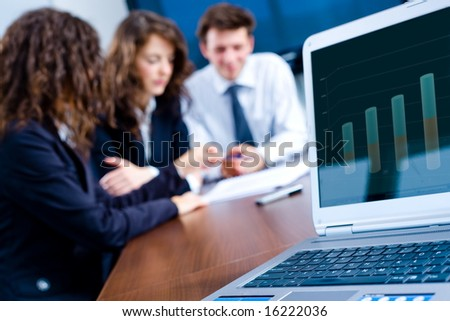 In background happy young business people having meeting at office. In front focus placed on graph showing progress on laptop screen.