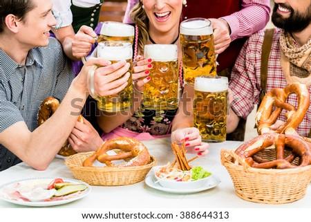 In Beer garden - friends in Tracht, Dirndl and Lederhosen drinking a fresh beer in Bavaria, Munich, Germany ストックフォト ©