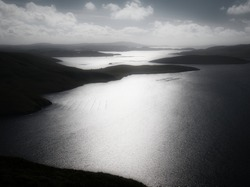 In black and white, a misty view of sunlight on the water of Olna Firth from the hillside of the Clubb of Mulla near Voe in Mainland, Shetland, UK. The island of Muckle Roe appears in the distance.