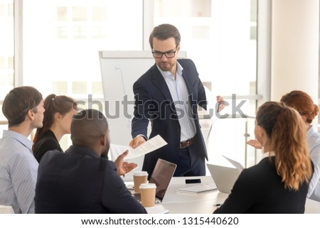 In boardroom gathered multiracial business people in formal wear, confident caucasian coach giving handout or financial report to diverse seminar participants. Information, education teamwork concept