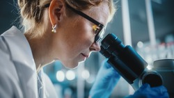 In Bright Medical Science Laboratory: Beautiful Microbiologist Wearing Glasses Looks Under Microscope Analyzing Sample. Brilliant Scientist, Doctor, working with High-Tech Equipment. Close-up Shot